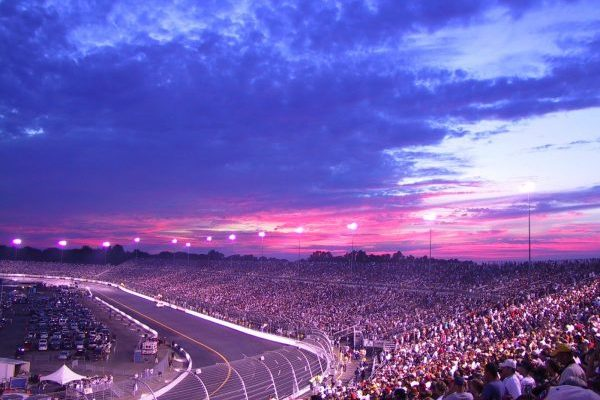 Richmond, VA blue, pink, and fuschia sunset over oval raceway with stands packed with NASCAR fans.