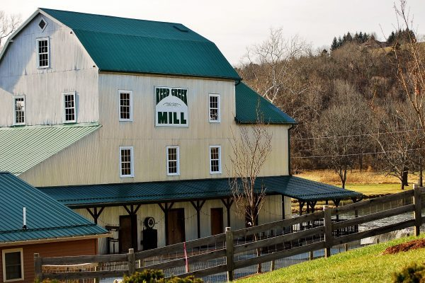 Wytheville, VA Reed Creek Mill, a tall, antique, wooden framed, metal sided structure beside running river.