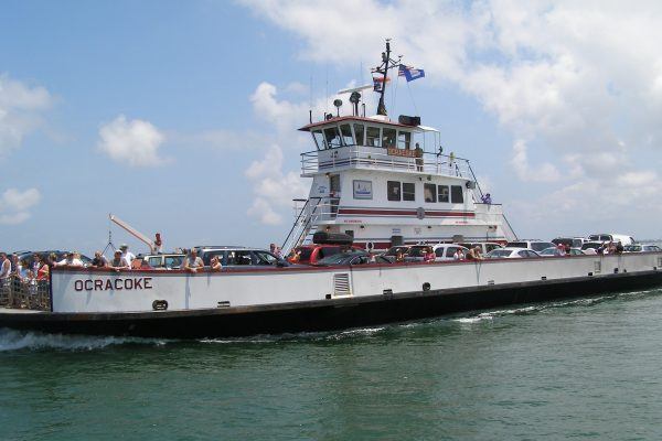 Outer Banks, NC white ferry filled with vehicles and passengers peering over sides. Vessel name is Ocracoke.