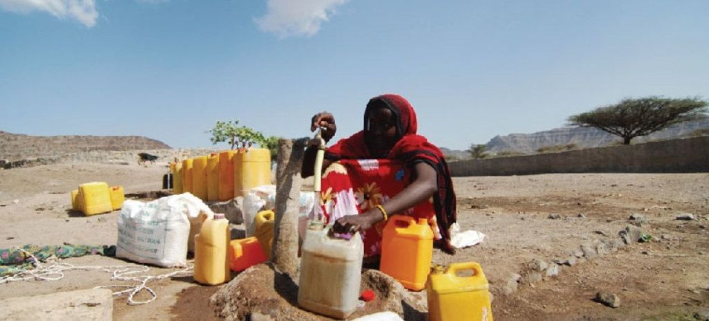 Woman collecting  water in desert