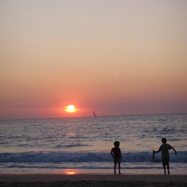 Enfants jouant devant le coucher de soleil