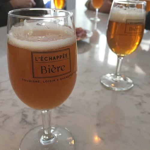 Verre de bière plein avec le logo de l'Échappée Bière