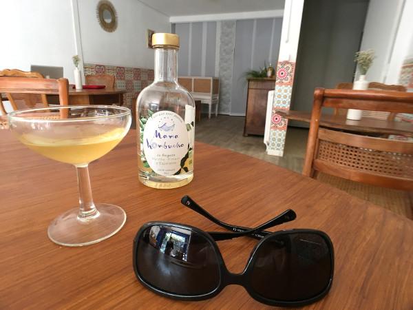 Une coupe de kombucha sur une table avec une bouteille et des lunettes de soleil
