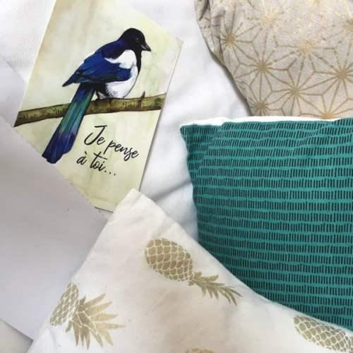 carte postale posée sur un canapé avec des coussins
