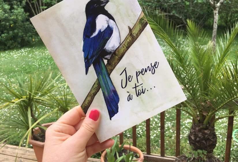 Main tenant une carte postale avec un oiseau