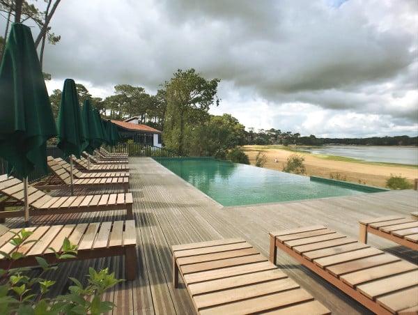 Piscine à débordement et terrasse de l'hôtel Les Hortensias du Lac surplombant le lac d'Hossegor