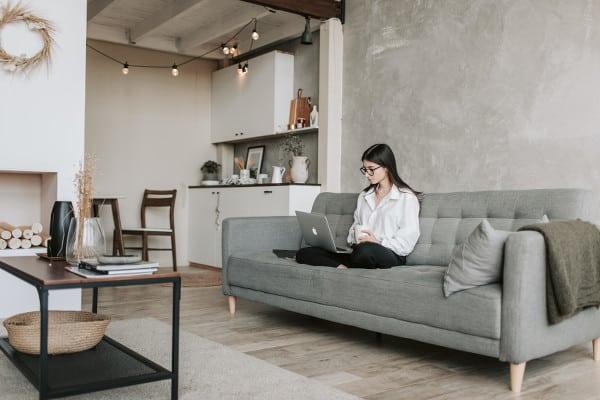 femme lisant les articles de blog sur son canapé