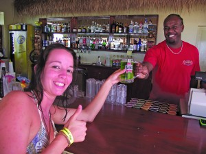 German visitor Susanne Wessely is handed her very first mug of green Banks Beers from Marlon Brathwaite, bar manager of Tiki Bar.
