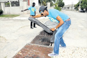 Men place a tarpaulin over a draw in a bid to suppress the stench from the sewage on Maize Avenue in Duhaney Park, St Andrew, on Tuesday. The residents say the problem has persisted for years.