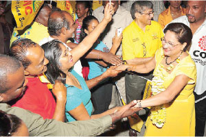 United National Congress supporters greet Prime Minister Kamla Persad-Bissessar on her arrival at the party's Monday Night Forum last night. Her husband Dr. Gregory Bissessar is on her right. Sport Minister Anil Roberts is behind the prime minister.