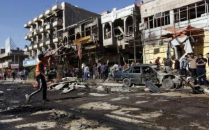 Residents gather at the site of a car bomb attack in the AL-Mashtal district in Baghdad today.