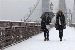 Women walk on the Brooklyn Bridge during a snowstorm in New York today.