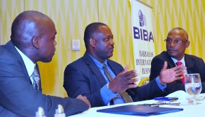 Minister of International Business, Donville Inniss making a point to BIBA's Executive Director, Henderson Holmes (right) and First Vice President, Ryle Weekes at BIBA's luncheon at Hilton today.