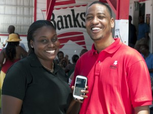 A proud Shernelle Knight (left) displays her new Samsung Galaxy SII in the company of Charles Walcott, category manager for Banks Holdings Limited.