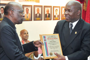 Senior Superintendent Vincel Edwards, right, receives a ministerial award on behalf of the Fraud Squad from National Security Minister Jack Warner, who hosted a ceremony to honour police officers, soldiers and immigration officers at the Ministry of National Security yesterday.