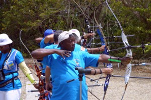 President of the Barbados Archery Association John Annel (foreground) and other archers going for the target.