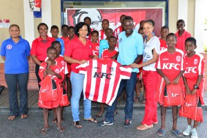 KFC's Andrena McCarthy presenting one of the football jerseys to Fernando Best and St. Michael South East MP Santia Bradshaw, while team members look on.