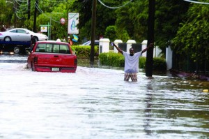 A citizen gestures in floodwaters after heavy rains battered the island chain yesterday.