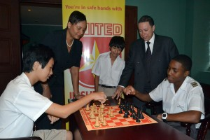 Yu Tien Poon (left) and Allon Richards play a challenge match while watched by United Insurance's Sharon Alleyne-Elcock, chess federation president Alan Herbert and Luke Cordozo.