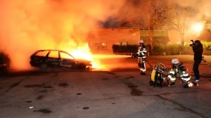 Firemen attend to a burning car in Stockholm yesterday.
