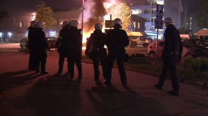 Swedish police look at a fire set by protesters.