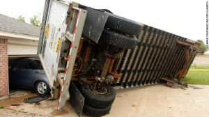 A trailer rests against a garage in Cleburne, Texas today after being blown into a house.