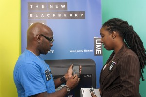 Kadri Walcott, winner of the LIME BB Z10 promotion, demonstrating one of the games he developed to Carolyn Williams-Gayle, corporate communications manager, LIME.