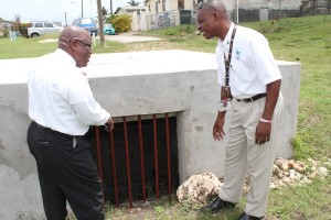 Minister Lowe and Terrol Inniss (right) at the well constructed in Thorpes.