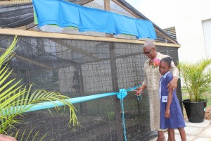 Judith Sealy, assisted by nine-year-old Christina Clarke, cuts the ribbon to declare the Ashantio Sealy Greenhouse open.