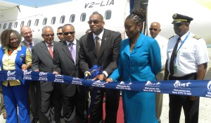 Minister of Tourism, Richard Sealy (third from right) is assisted by Parliamentary Secretary in the Ministry of International Transport, Senator Irene Sandiford-Garner in cutting the ribbon to welcome the new LIAT plane at Grantley Adams International Airport today. Looking on are LIAT Chairman, Jean Holder (fourth from right), CEO Ian Brunton and other officials.