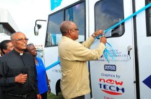Minister John Boyce cuts ribbon for new diabetes bus.