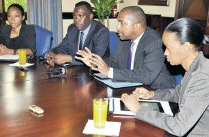 Julian Robinson (right), minister of state in the Ministry of Science, Technology, Energy and Mining, gestures as Inspector Warren Williams, head of the police Cybercrimes Unit listens.