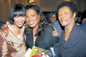 Prime Minister Portia Simpson Miller (left) gets a hug from Jamaican actress Sheryl Lee Ralph, while the actress' mom, Ivy, shares the moment.