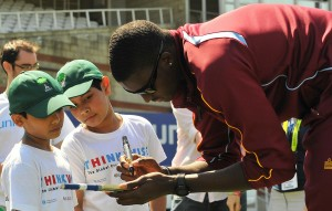 Jason Holder signs an autograph for one of the children.