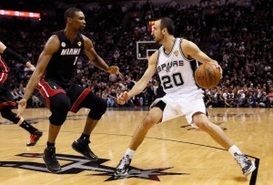Spurs' Manu Ginobili (with ball) is defended by the Heat's Chris Bosh.