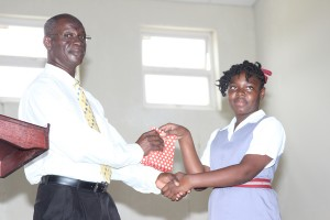 Representative from the Ministry of Education Ovid Gibbs being presented with a token of appreciation from student Leann Scantlebury.