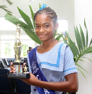 Valedictorian Amicha Coward appears pleased with her trophy for academic excellence.