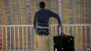 A traveller looks at a flightboard at a French airport.