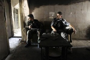 Members of the Free Syrian Army sit on a sofa inside a house in the old city of Aleppo June 19, 2013.
