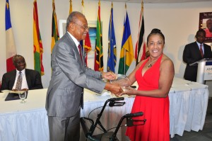 Rose-Ann Foster-Vaughan receives her award from Acting Governor General Sir Phillip Greaves.