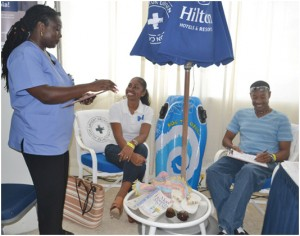 Patrons at BMEX, Kimberly Angoy and Herbert Reifer (both seated) being diagnosed at the Hilton Barbados Resort mobile cure zone, by vacation care specialist, Kathy-Ann Selman.