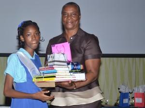 Valedictorian Brianna Gittens accepting her bundle of prizes from Hazel Worrell.