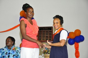 Valedictorian Kishanna Williams receiving a plaque for academic excellence.