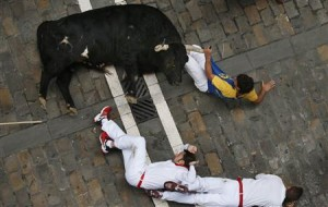 A runner holds the horn of an El Pilar fighting bull after falling on Estafeta street, and before being gored by the same bull, during the sixth running of the bulls of the San Fermin festival in Pamplona today.