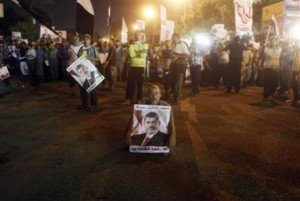Mursi supporter holds a poster and sits at a street during an anti-army rally in Cairo