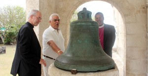 The Archbishop, Justin Welby and Reverend Dr. John Holder looking at a dated bell.