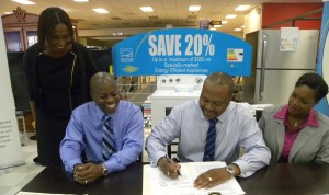 CEO of the EGFL, Timothy Symmonds (centre) signs the agreement to get the initiative going, while Executive Director of DaCosta Mannings Retail, Paul Rowe and Project Manager of the Energy Smart Fund, Keisha Reid look on.