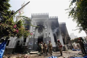 Members of military police stand outside the burnt Rabaa Adawiya mosque in Cairo