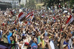 Supporters of deposed President Mursi shout slogans and wave Egyptian flags during protest outside Al-Fath Mosque in Cairo