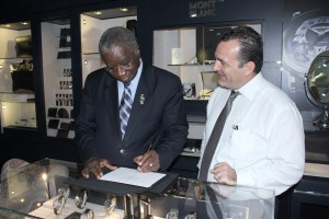 The Prime Minister testing a classic Mont Blanc pen as Managing of Diamonds International, Jacob Hassid looks on.